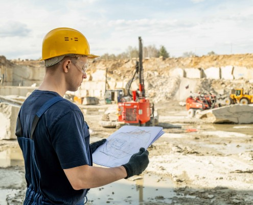 Young builder in workwear holding sketch of construction